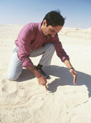 Qurian drawing a map in the sand