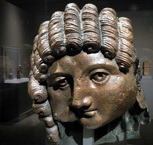 A cast bronze head, originally part of a life-size statue. The sensitive face recalls Greco-Roman models, while the curls are more typical of southern Arabian workmanship. It may be from the first or second century A.D. Photo by J. Pint